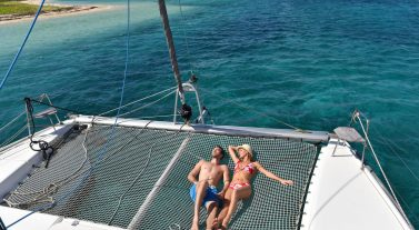 couple relaxing on the net of the bow