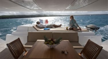 couple relaxing on the stern of the moving boat