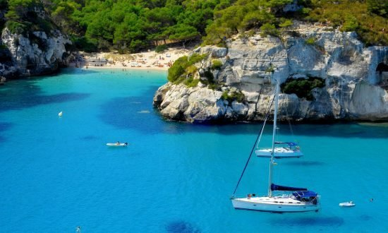 boats passing hidden beach in Balearic Islands