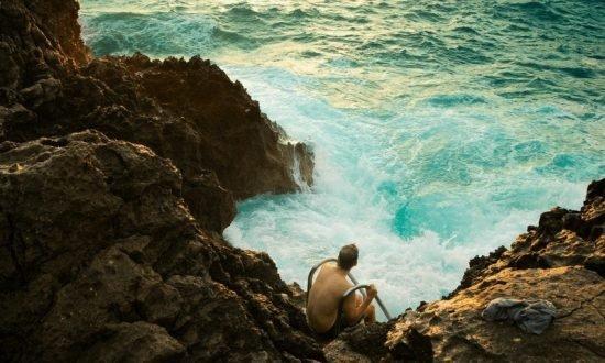 man sitting on rocks edge with waves crashing around rocks
