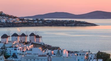 view of houses stores and the water of windmill Bay Mykonos Greece