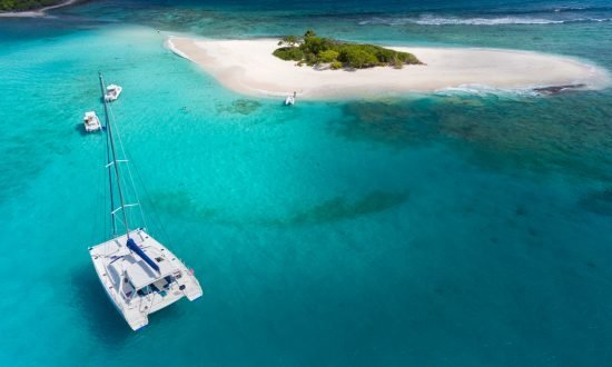 Sailboat anchored in front of deserted island BVI