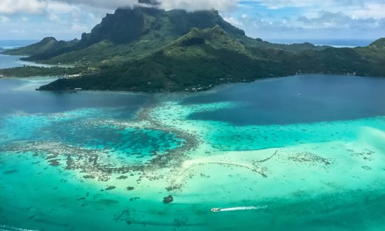 Lagoon of Bora Bora aerial with boats to Mount Otemanu