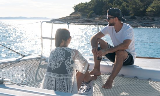 Couple relaxing on deck of yacht with drink